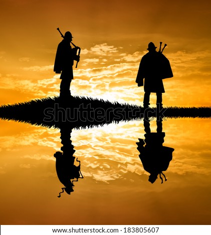 two pipers playing the bagpipes at sunset - stock photo