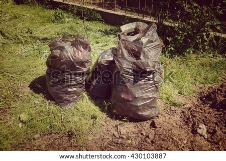 Two plastic bags of garbage on the grass - stock photo