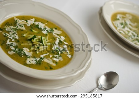 Two plates of cucumber cream soup garnished with cream, parsley and fine cut cucumbers on a white tabletop. A concept of a healthy appetizer meal. A concept of vegetarian food. Horizontal orientation. - stock photo