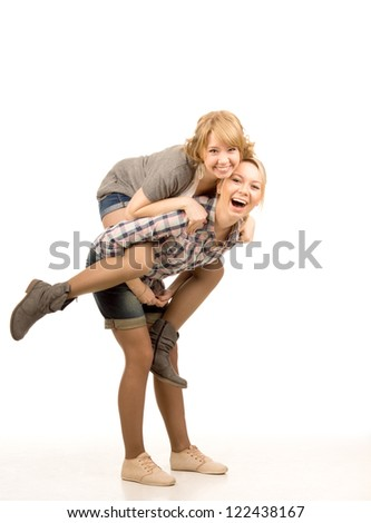 Two playful attractive young female friends laughing and having fun together as the one gives the other a piggyback ride isolated on white - stock photo