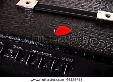 two plectrums on black guitar amplifier - stock photo