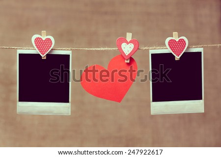 Two polaroid photo frames and heart for valentines day hanging on vintage background with vintage instagram toning - stock photo