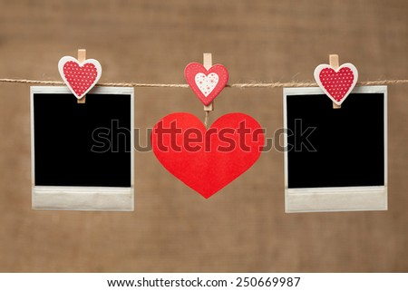 Two polaroid photo frames and red heart for valentines day hanging on vintage background - stock photo
