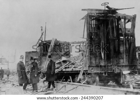 Two policemen and a civilian survey the ruins along the Lehigh Valley Railroad tracks where boxcars were riddled by exploding shells from munitions at Black Tom Island port facilities. June 30 1915. - stock photo