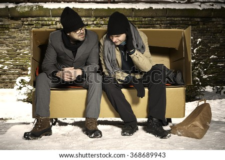 Two poor men living in paper box on bench in winter park - stock photo