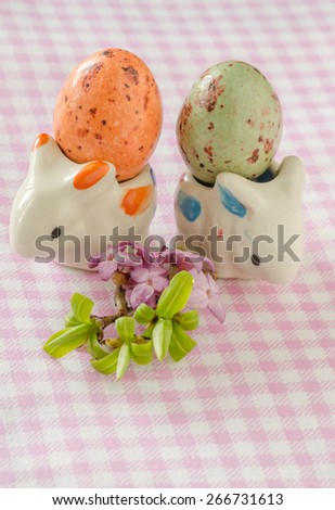 Two porcelain rabbit with eggs and small bouquet of beautiful flowers. Easter still life. - stock photo