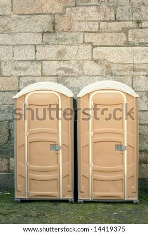 Two portable toilets, porta potty, against stone wall - stock photo