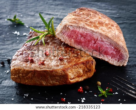 Two portions of lean trimmed grilled beef steak cut through to show the succulent tender red meat and seasoned with rosemary, salt and pepper in a steakhouse or restaurant - stock photo