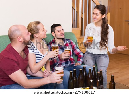 Two positive couples hanging out with beer and snacks at at house party together - stock photo