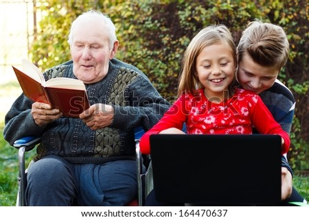 Two possibilities of entertainment - read a book or use a laptop. - stock photo