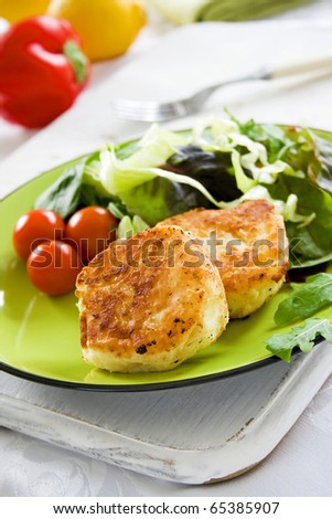 Two potato cakes on a plate with fresh green salad - stock photo