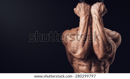 Two Power Hands in Front of Face. Close-up of a man's fists and abs. Strong man's arm with muscles and veins. Photo with copy space - stock photo