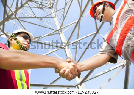 two power line tower workers with handshaking - stock photo