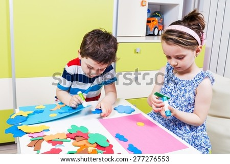 Two preschool child create a picture with foam shapes - stock photo