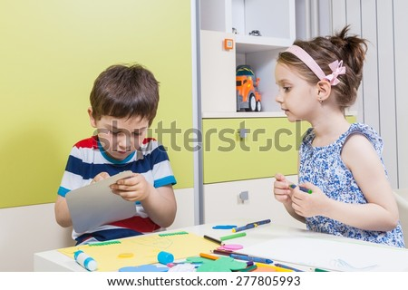 Two preschool child working for homework received from kindergarten - stock photo