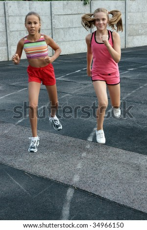 Two preteen girls running on track - stock photo