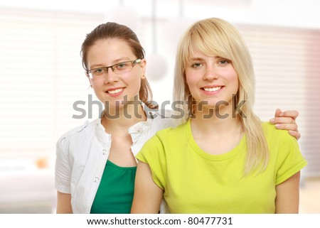 Two pretty college girls lying on the floor - stock photo