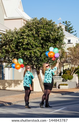 two pretty friend in matching clothing walking down a street holding balloons and looking back smiling - stock photo