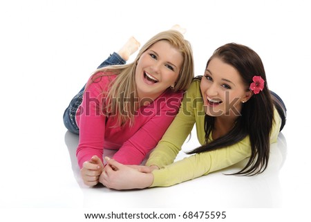 Two pretty girl friends having fun and laughing on the floor. isolated on white background - stock photo