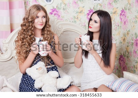 Two pretty girl-friends talk and drink tea .Happy girls drinking tea and gossiping in home. Two girlfriends blonde and brunette drinking tea in bed and talking. Teenage girls discuss boys - stock photo