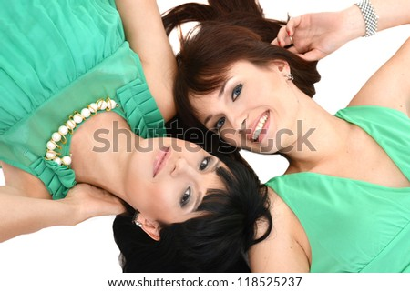 Two pretty girlfriend in green dresses lie on a white background - stock photo