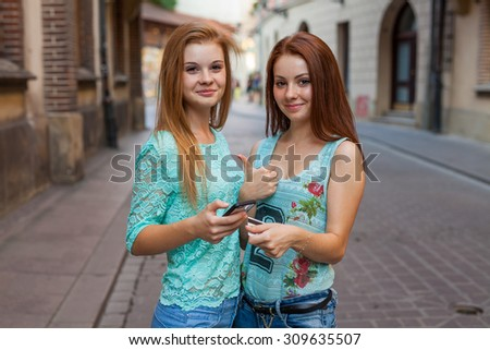 Two pretty girls holding smartphone and credit card. Urban background - stock photo