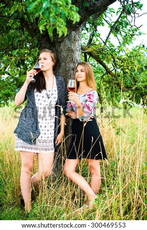 Two pretty girls in the garden under a tree drinking wine and looking cool - stock photo
