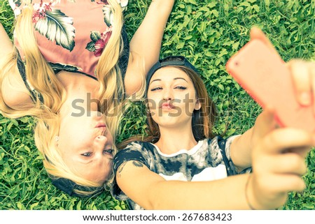 Two pretty girls taking a self portrait - Young women with a sportive casual outfit lying on meadow and having fun while taking a selfie - stock photo