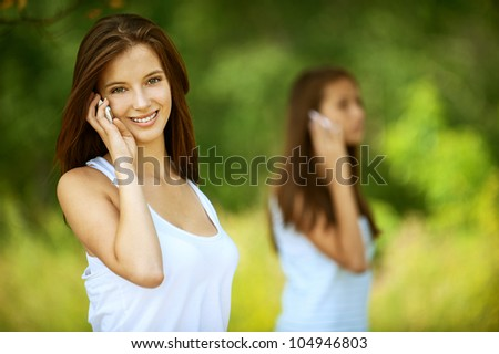Two pretty girls talking on cell phone, against green of summer park. - stock photo