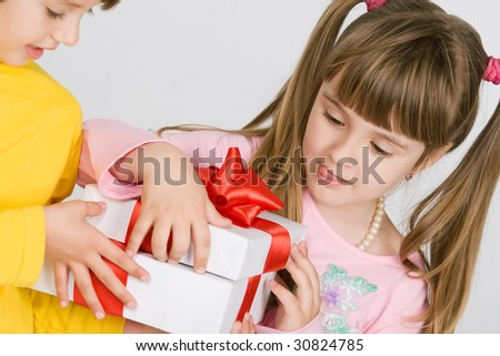 Two pretty little girls holding gift box - stock photo