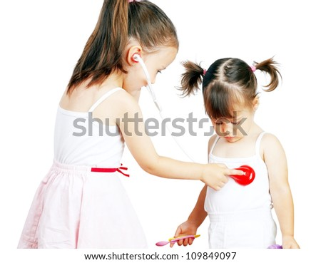 Two pretty little girls playing doctor - stock photo
