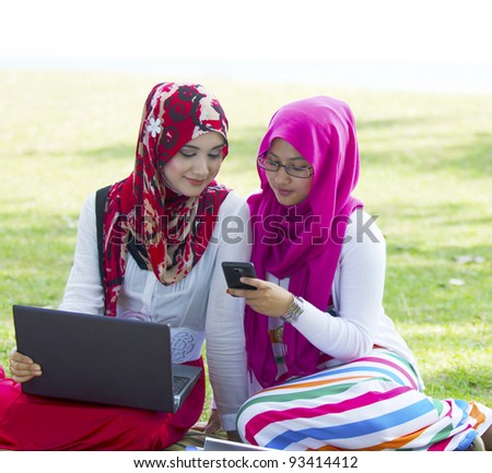Two pretty Muslim lady in conversation while surfing internet using notebook and smartphone. - stock photo