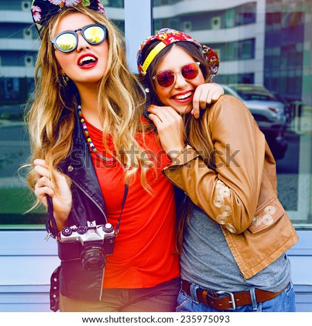 Two pretty sisters hipster girls hugs and having fun together, wearing bright trendy clothes and swag hats, holding vintage camera, ready for shooting, positive emotions, bright colors. - stock photo
