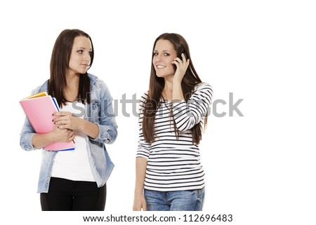 two pretty student friends calling by phone on white background - stock photo