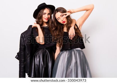 Two pretty stylish girls have fun and laughing. Best friends  in fall outfit posing in studio.Perfect wavy hairstyle.  - stock photo