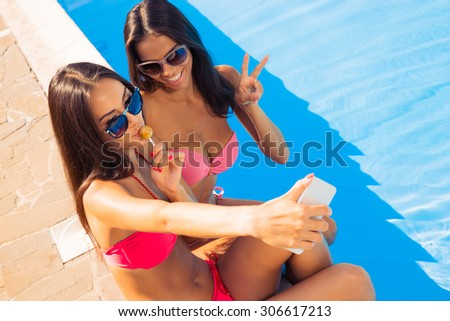 Two pretty woman in swimsuit making selfie photo on smartphone outdoors - stock photo
