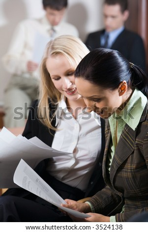 Two pretty women reading notes and two reading men on the background - stock photo