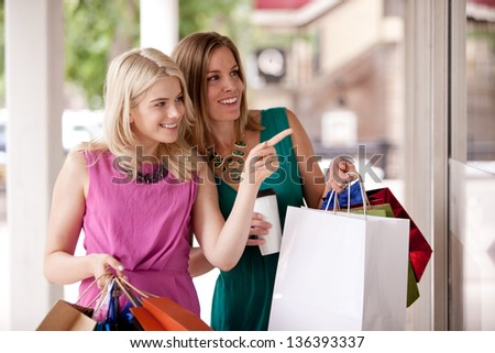 Two pretty women windows shopping in a down town city - stock photo