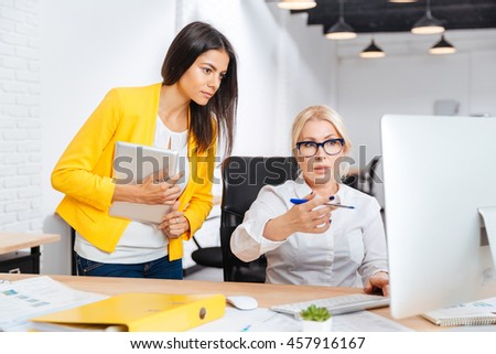 Two pretty young and mature office women having a brainstorm meeting at the table in the office - stock photo