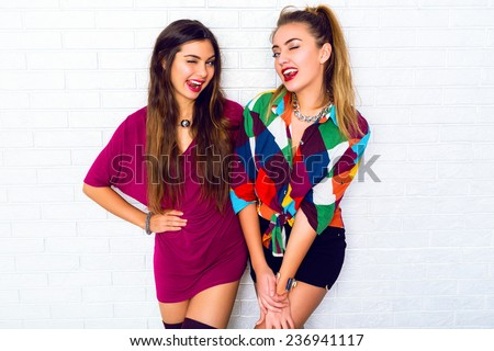Two pretty young emotional women friends showing tongue and winked , wearing bright stylish casual clothes and bright make up. Urban white background. - stock photo