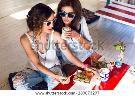 Two pretty young friends girls having lunch together in cute cafe, smiling speaking and gossip, wearing bright clothes and accessories. - stock photo