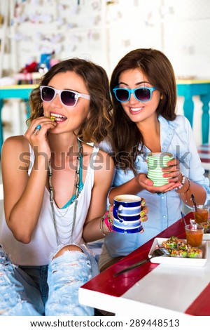 Two pretty young friends girls taking lunch in cafe, smiling gossip having fun, bright clothes, joy, great time together. Cute come interior, sunny colors. - stock photo