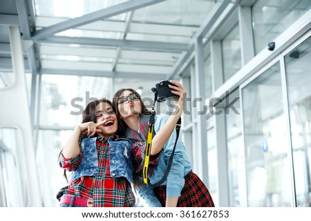 Two pretty young girl laughing and posing to take a selfie with a digital camera, wearing stylish clothes and fashionable glasses.  Having fun.  - stock photo