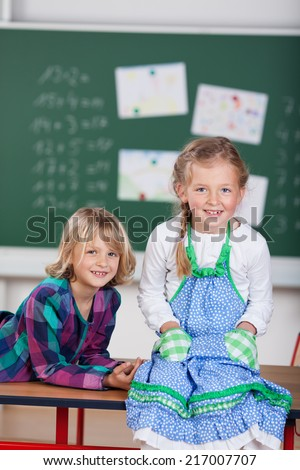 Two pretty young girls attending school sitting relaxing on top of a desk in front of the blackboard grinning happily at the camera - stock photo