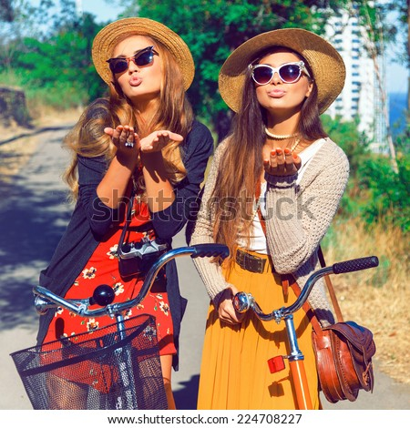 Two pretty young happy girls send you air kiss, wearing vintage stylish clothes hats and sunglasses, having fun together and walking with retro bikes. Fashion outdoor portrait of two sisters. - stock photo