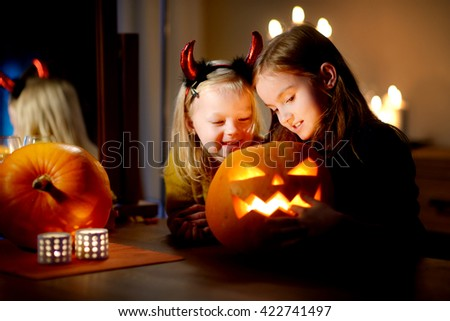 Two pretty young sisters in halloween costumes carving a pumpkin together on Halloween - stock photo