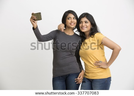Two pretty young women taking selfie with mobile phone - stock photo
