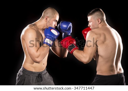 Two professional boxer isolated on black background - stock photo