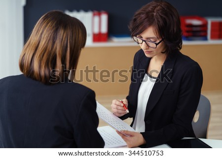 Two Professional Businesswomen in Black Suits Having a One-on-One Business Meeting Inside the Office. - stock photo