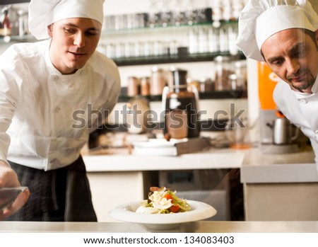 Two professional male chefs in restaurant kitchen. - stock photo